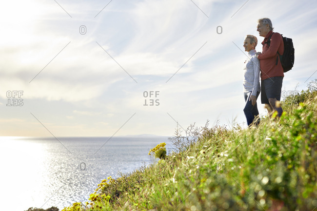 Side view of senior couple looking at sea while standing on cliff against sky