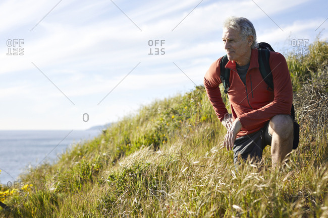 Senior man kneeling by plants on cliff against sky during sunny
