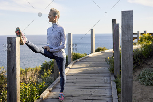Full length of senior woman doing stretching while standing on boardwalk by sea against sky
