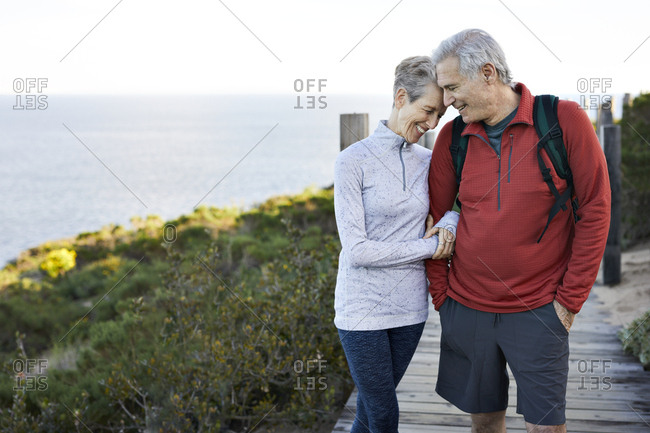 Happy senior couple with arm in arm standing on boardwalk by sea against sky