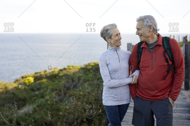 Smiling senior couple with arm in arm looking at each to other while standing on boardwalk by sea against sky