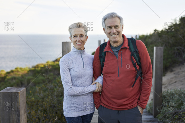 Portrait of smiling couple standing against sea