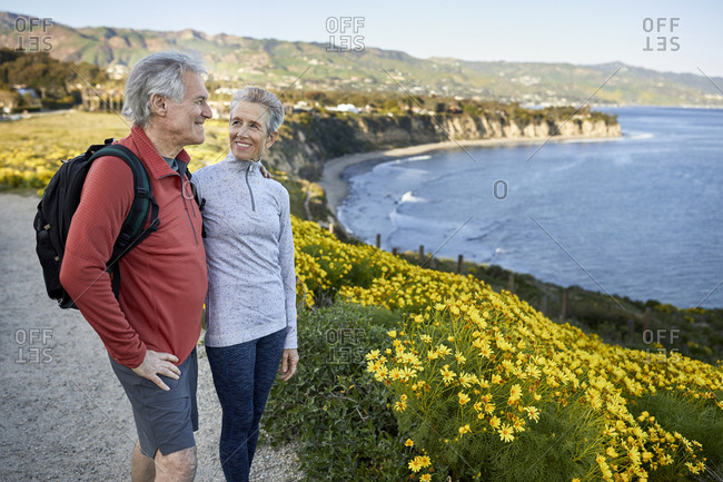 Smiling senior woman looking at man while standing by flowering plants on cliff at beach