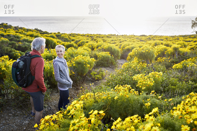 High angle view of senior couple talking while standing on trail by flowers plants against bright sky
