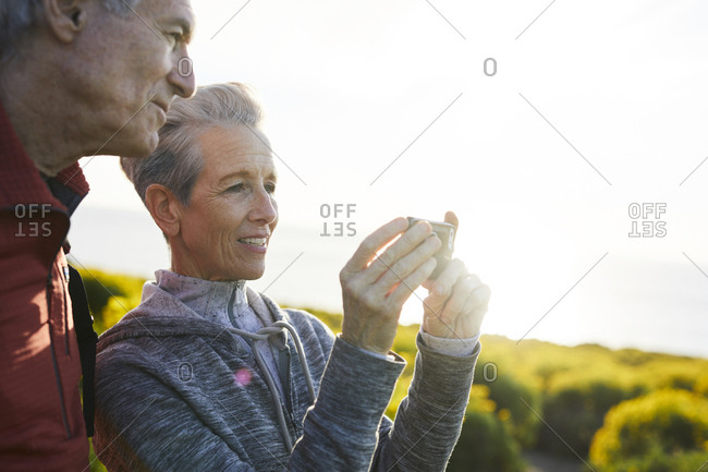 Smiling man standing by senior woman photographing through smart phone while standing against clear sky