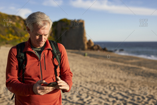 Senior man using smart phone while standing at beach during sunny day