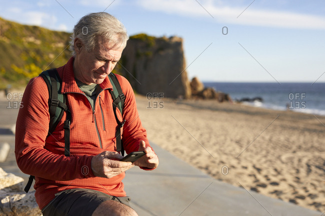 Senior man using smart phone while standing at beach