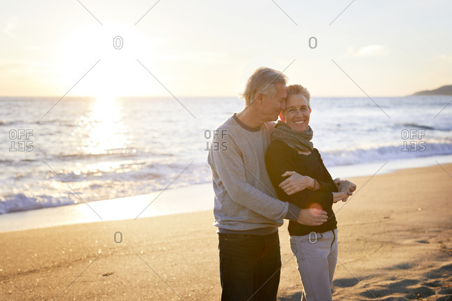 Affectionate senior couple standing at beach during sunset