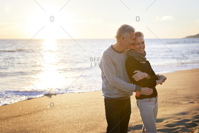 Affectionate senior couple standing at beach against sky during sunset