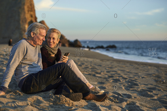 Senior couple using phone while sitting on sand at beach during sunset