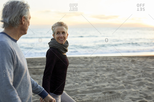 Side view of senior couple holding hands while walking at beach during sunset
