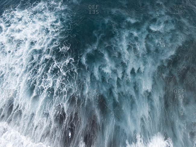Aerial view of ocean surface, waves, white water and surfers