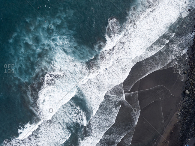 Aerial view of beach and shoreline, waves and surfers
