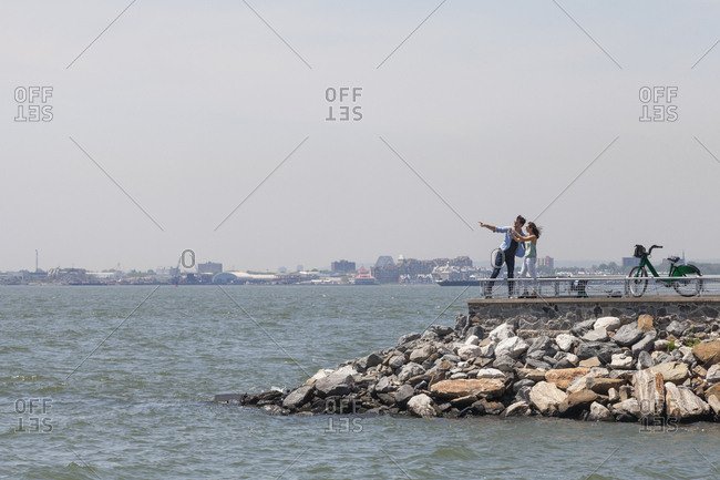 Couple standing on observation point by river against clear sky