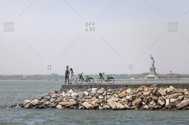 Couple standing on observation point with Statue of Liberty in background against clear sky