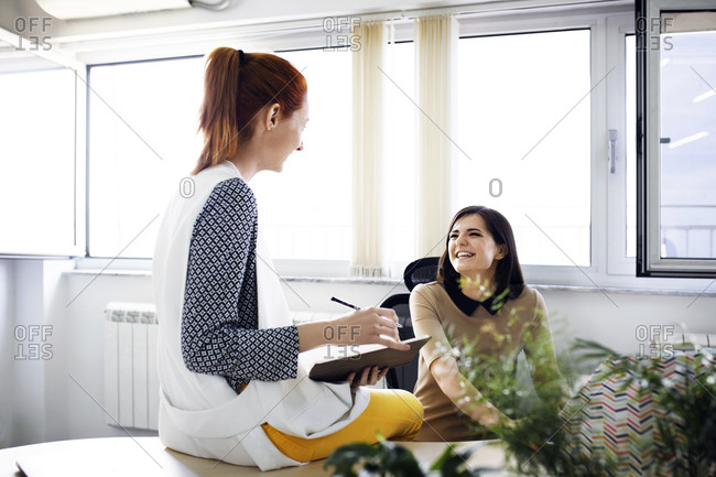 Happy businesswomen discussing in creative office