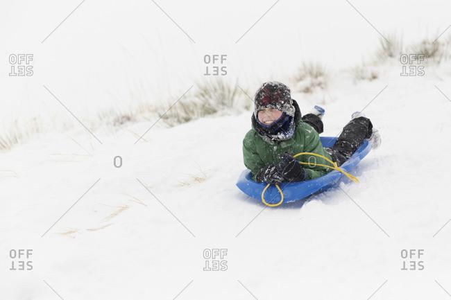 Teenage boy sledding on snow covered landscape during winter
