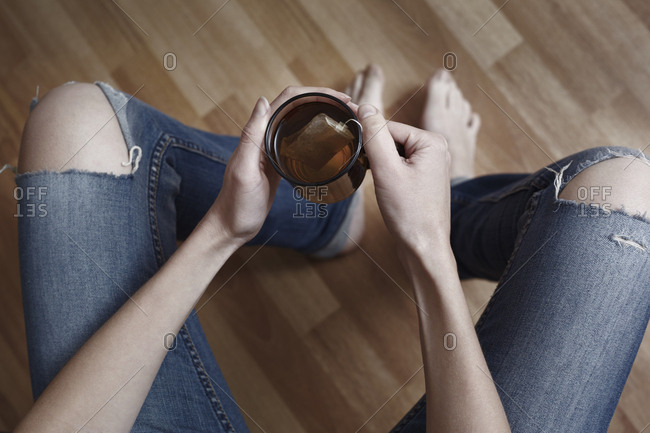 High angle view of woman holding tea cup at home