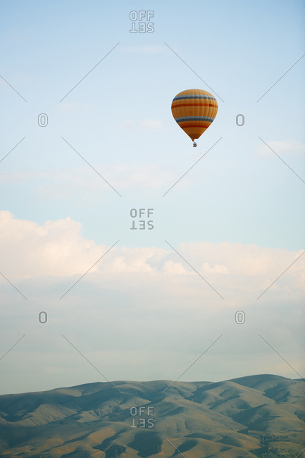 Hot air balloon flying over the hills