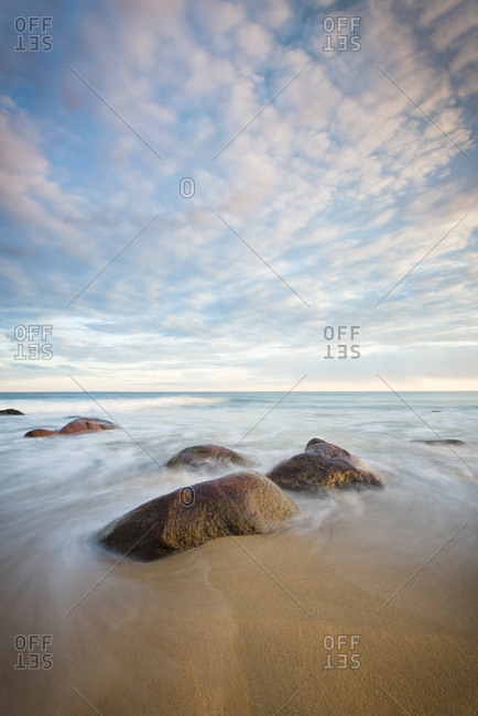 Rocks at shore against cloudy sky