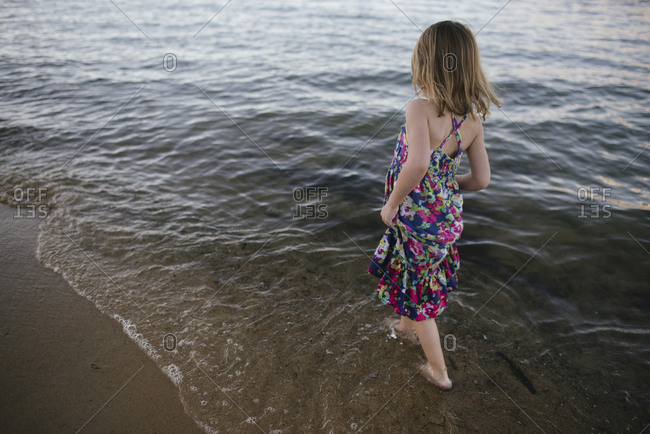 Rear view of carefree girl walking in sea on shore at beach