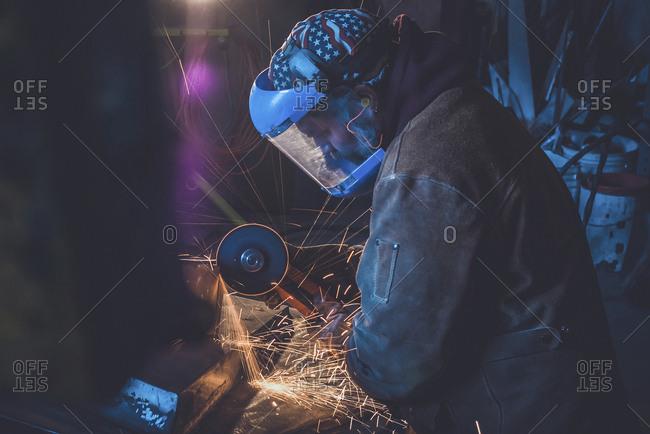 Side view of welder working in workshop