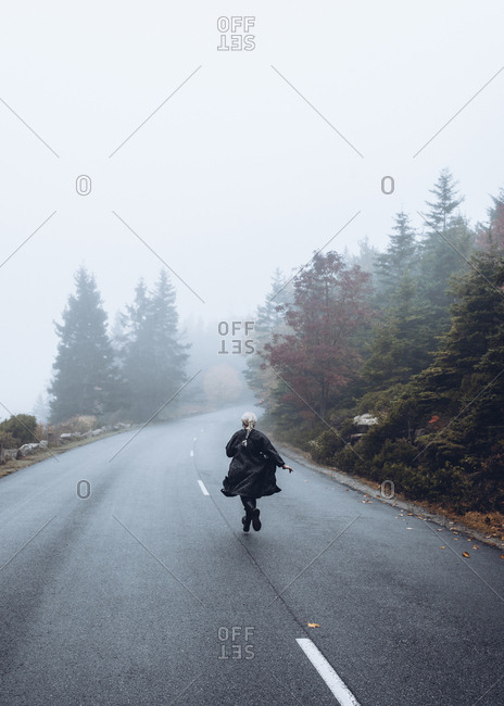 Rear view of woman running on road against sky during foggy weather