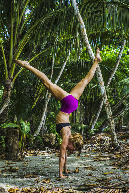 Side view of fit woman performing handstand in forest