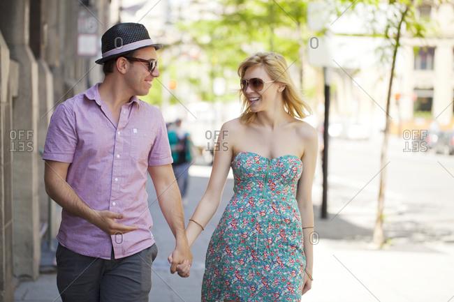 Young couple walking on street flirting
