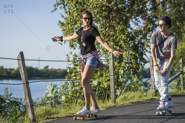 Couple cruising down bike path together on skateboard