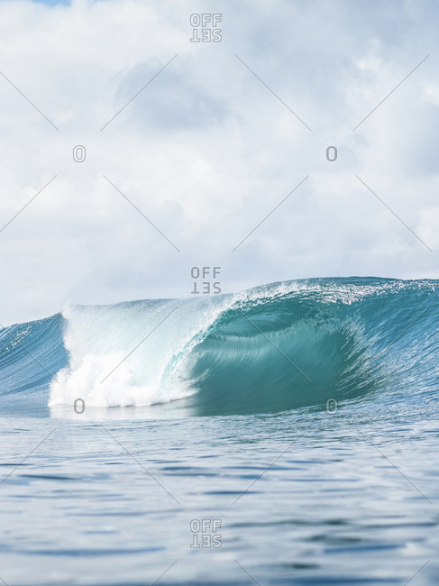 Waves breaking in sea against sky