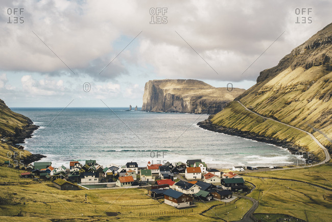 High angle view of village by coastline against cloudy sky