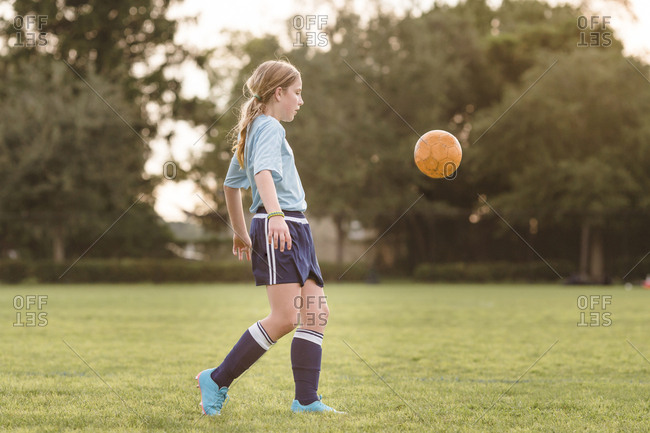 Side view of girl playing soccer at field