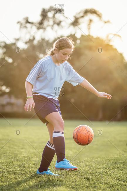 Girl kicking soccer ball while playing at field
