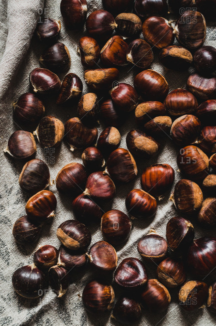 Whole sweet chestnuts on an old kitchen towel