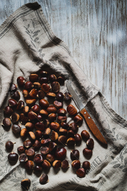 Whole sweet chestnuts on an old kitchen towel with wooden knife