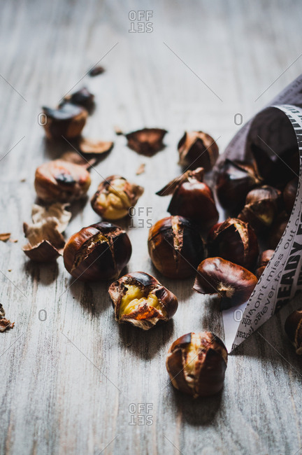 Roasted chestnuts falling out from paper cone