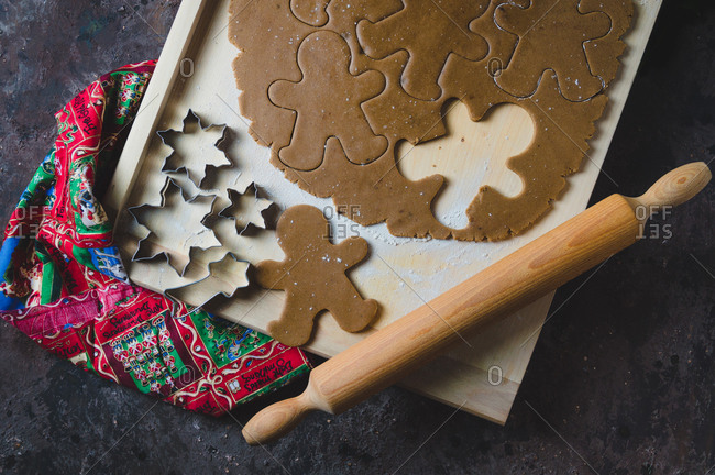 Top down view of gingerbread cookie dough, cookie cutters and rolling pin