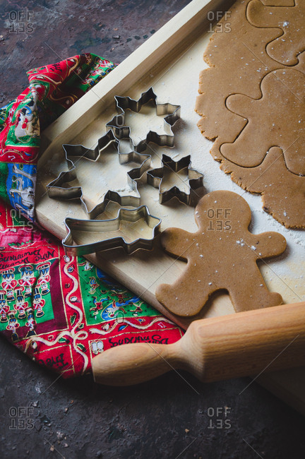 Close up of gingerbread cookie dough, cookie cutters and rolling pin
