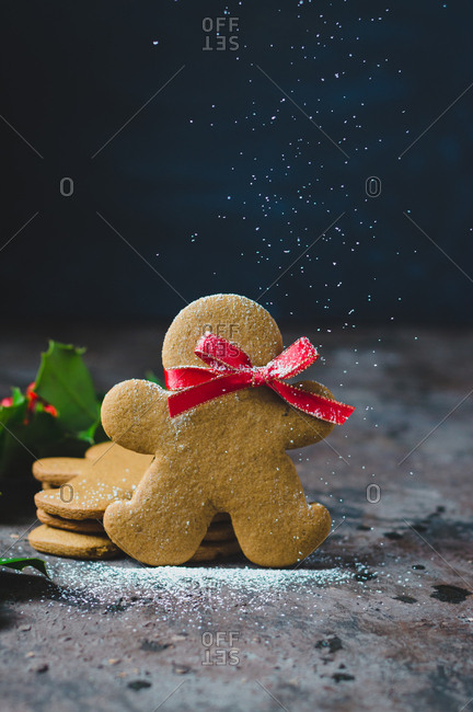Powdered sugar falling on single gingerbread cookie with a red bow