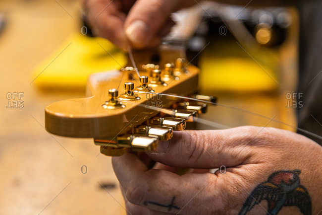 Luthier craftsman man repairing electric guitar in his workshop