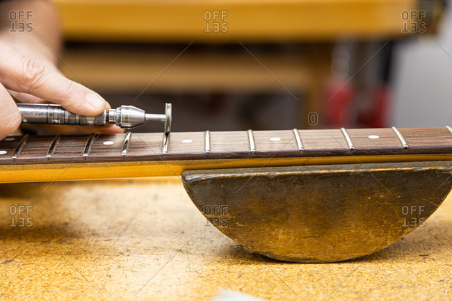 Luthier craftsman repairing the mast of an electric guitar in his workshop