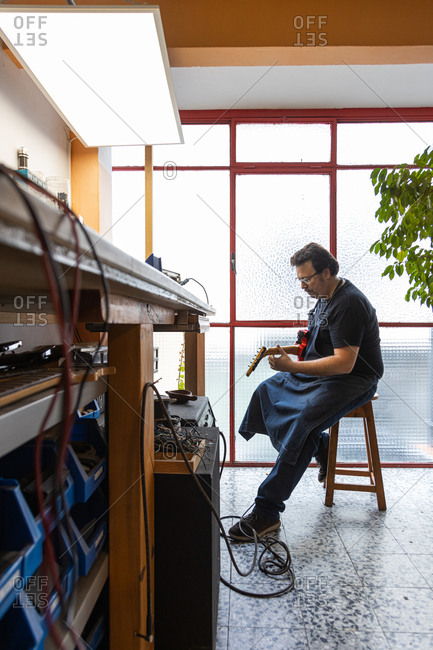 Luthier craftsman testing an electric guitar plugged into the amplifier