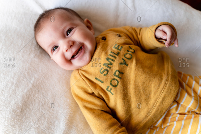 Happy three month old baby girl lying in bed and smiling