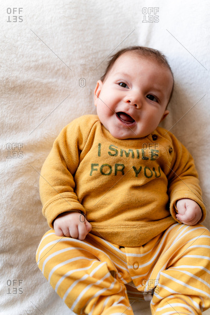 Portrait of happy three month old baby girl lying in bed and laughing