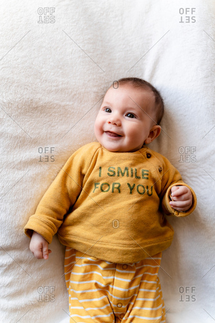 Portrait of happy three month old baby girl lying in bed and smiling