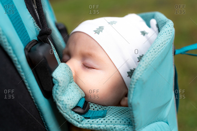 Sweet three month old baby girl sleeping in a blue baby carrier outdoors