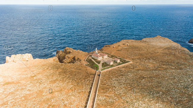 Aerial view of Punta Nati lighthouse at arid terrain, Balears Island, Spain.