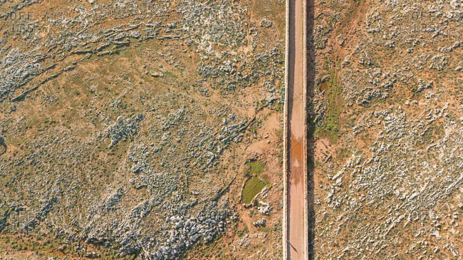 Aerial view of road crossing arid terrain at Balears Island, Spain.