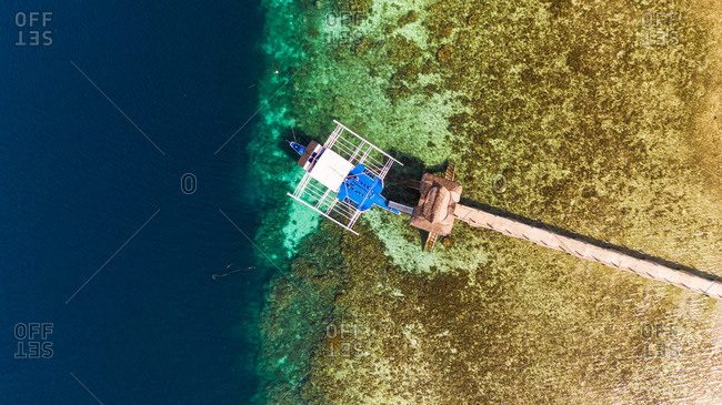 Aerial view of traditional boat anchored at pier, Starfish Island, Philippines.